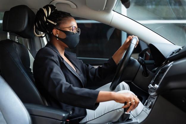 Vista lateral de la mujer con mascarilla conduciendo coche