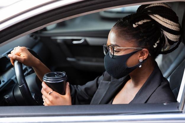 Vista lateral de la mujer con mascarilla tomando un café dentro de su coche