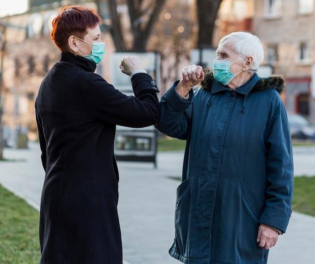 Vista lateral de una mujer mayor golpeándose los codos en la ciudad para saludarse