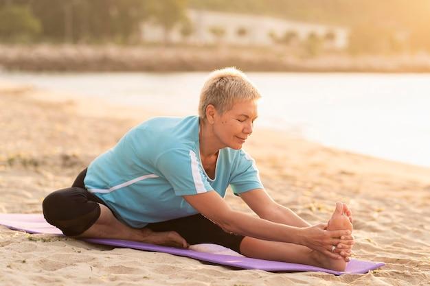Vista lateral de la mujer mayor haciendo yoga en la playa