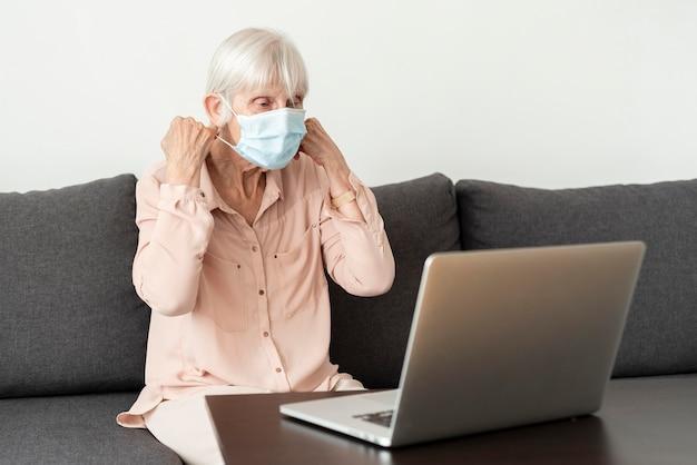 Vista lateral de la mujer mayor con laptop poniéndose mascarilla médica