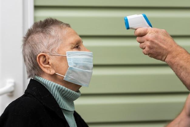 Vista lateral de la mujer mayor que controla su temperatura con termómetro