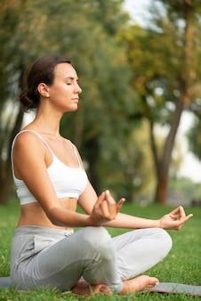 Vista lateral mujer meditando con los ojos cerrados