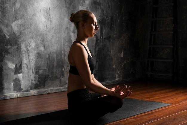 Vista lateral mujer meditando posición