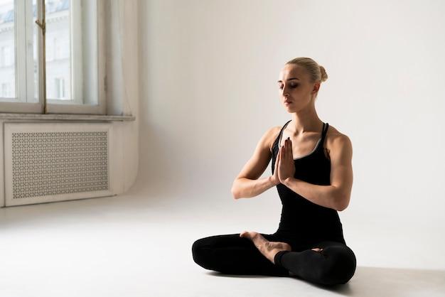 Vista lateral mujer meditando postura