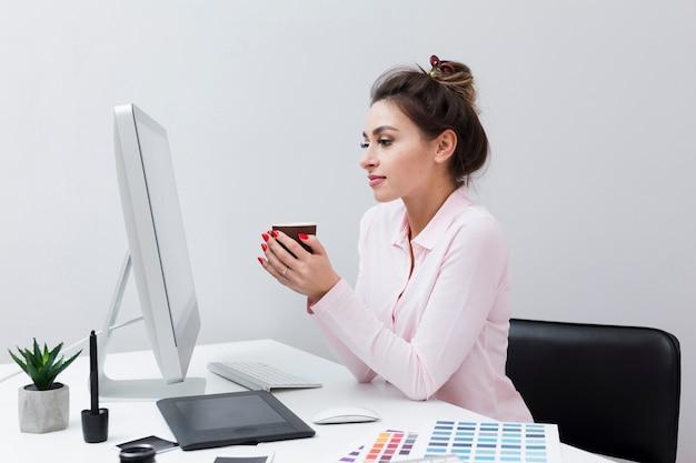 Vista lateral de la mujer mirando la computadora mientras sostiene la taza de café
