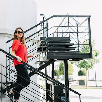 Vista lateral de una mujer de moda bajando la escalera