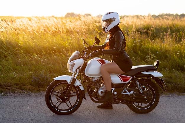 Vista lateral de la mujer montando motocicleta con casco