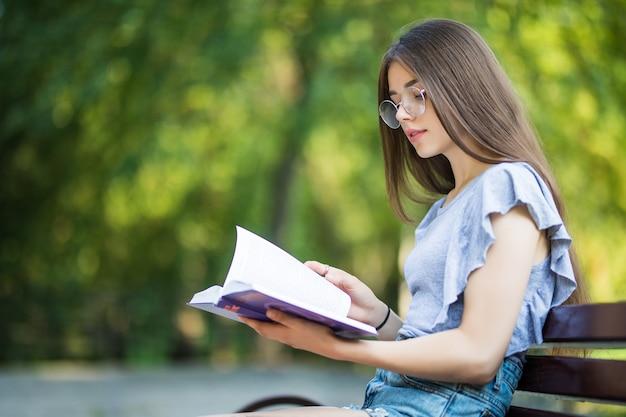Vista lateral de la mujer morena complacida en anteojos sentado en un banco y libro de lectura en el parque