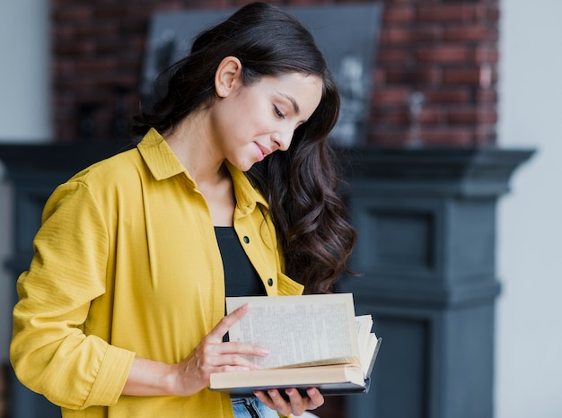 Vista lateral mujer morena leyendo en el interior