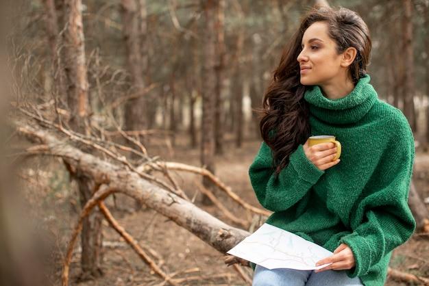 Vista lateral mujer en la naturaleza bebiendo té