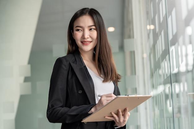 Vista lateral de una mujer de negocios asiática sosteniendo un documento de pie cerca de un espejo en una oficina.