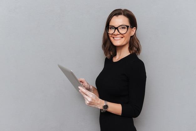 Vista lateral de la mujer de negocios feliz en anteojos usando computadora