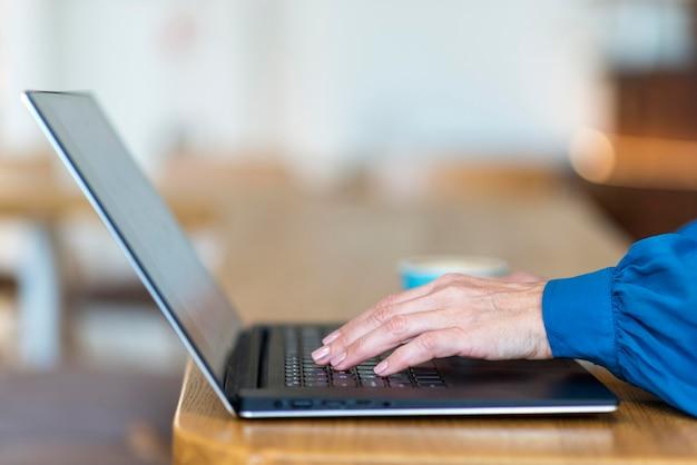 Vista lateral de la mujer de negocios mayor trabajando en equipo portátil