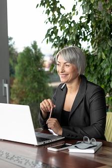 Vista lateral mujer de negocios sentado