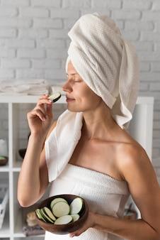 Vista lateral mujer oliendo rodaja de calabacín
