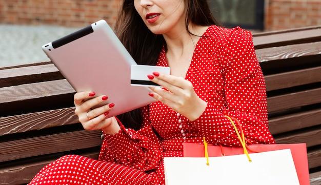 Vista lateral de la mujer con ordenador portátil y compra online con tarjeta de crédito