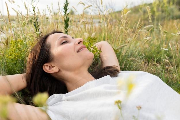Vista lateral de mujer en pasto al aire libre