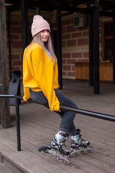 Vista lateral de la mujer con patines posando en la barandilla