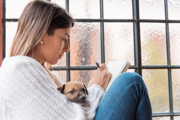 Vista lateral mujer con perro y bolígrafo