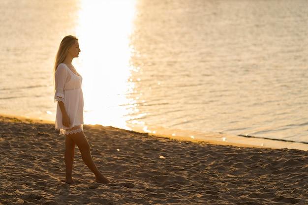 Vista lateral de la mujer en la playa al atardecer