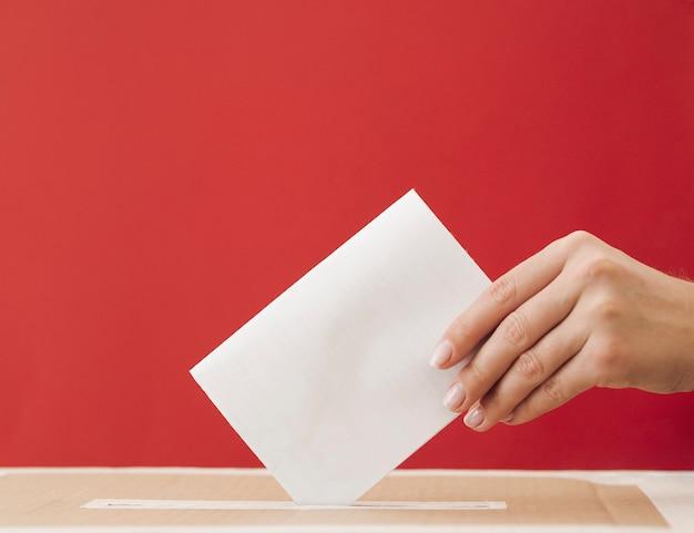 Vista lateral mujer poniendo una boleta en una caja con fondo rojo.