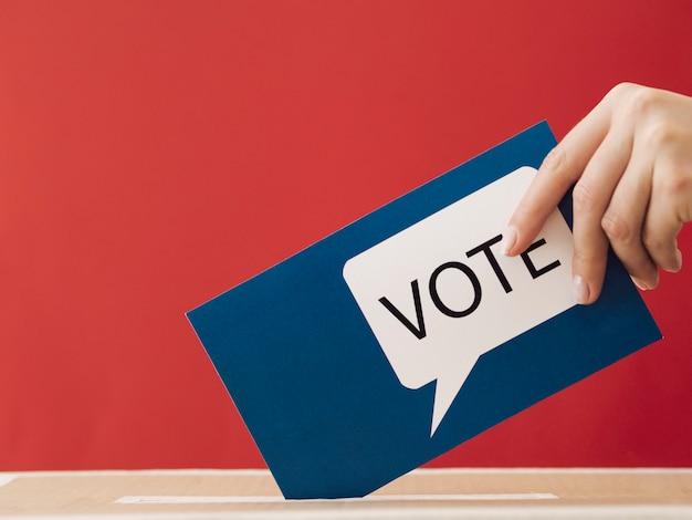 Vista lateral mujer poniendo una tarjeta de votación en una caja con fondo rojo.