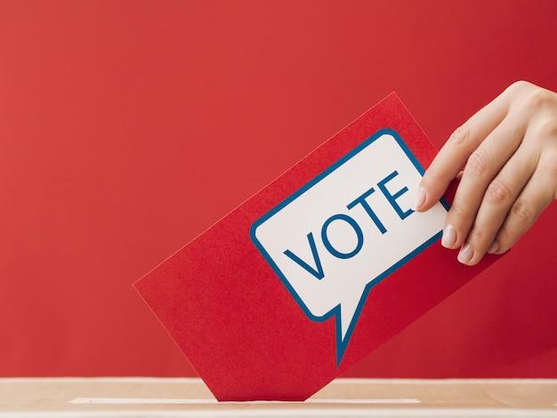 Vista lateral mujer poniendo una tarjeta de votación roja en una caja