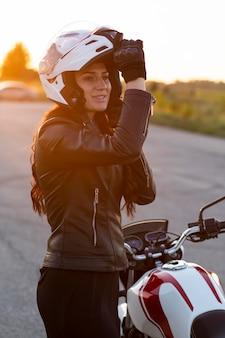 Vista lateral de la mujer poniéndose el casco para andar en motocicleta