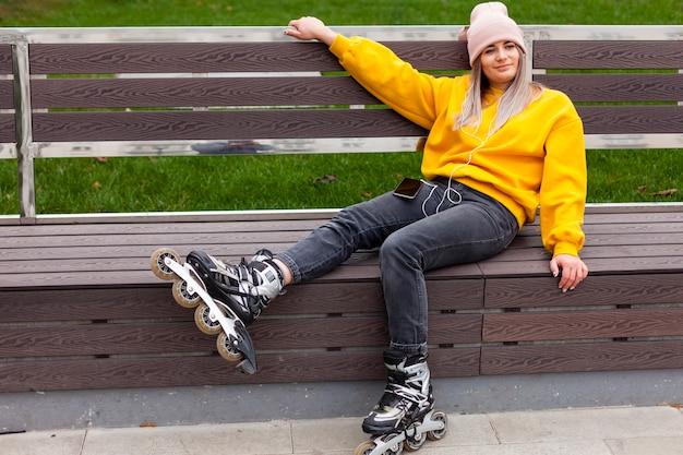 Vista lateral de la mujer posando en un banco con patines