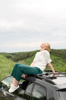 Vista lateral de la mujer posando encima del coche en la naturaleza
