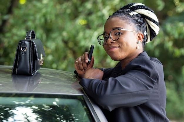 Vista lateral de la mujer posando junto a su coche con bolso encima