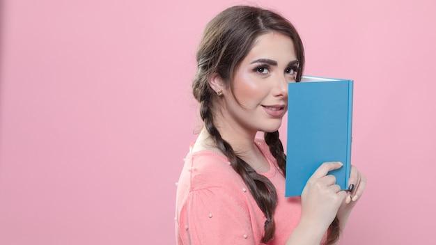 Vista lateral de la mujer posando con el libro cerca de su cara