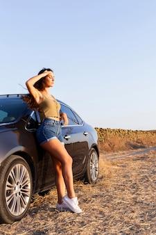 Vista lateral de la mujer posando mientras mira el sol y descansando en el coche