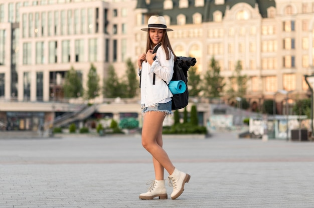 Vista lateral de la mujer posando mientras viaja sola con mochila