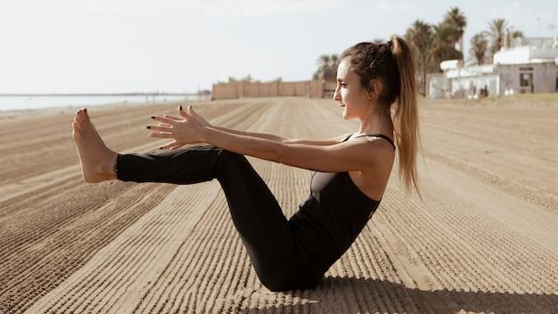 Vista lateral de la mujer practicando yoga en la playa