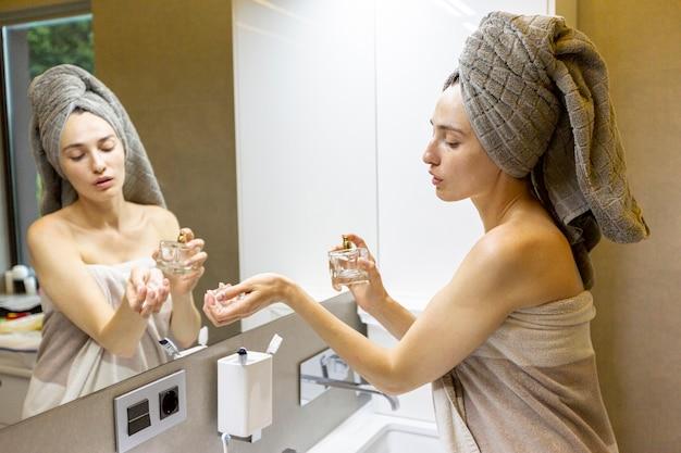 Vista lateral mujer probándose perfume