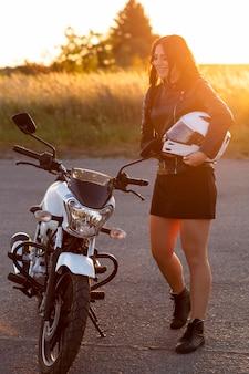 Vista lateral de la mujer en la puesta de sol junto a la motocicleta con casco