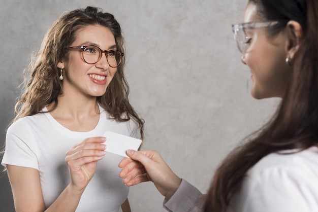 Vista lateral de la mujer que da la tarjeta de visita al empleado potencial