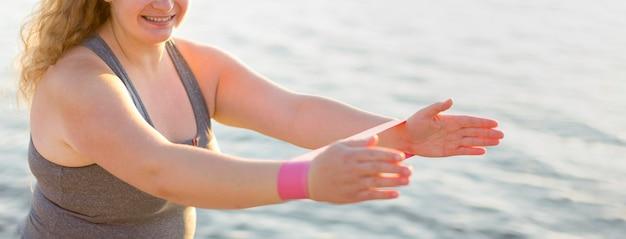 Vista lateral de la mujer que se ejercita junto al lago con bandas elásticas
