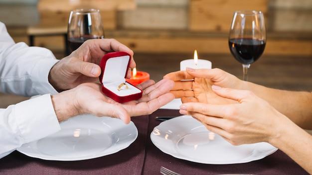 Vista lateral de la mujer que recibe un anillo de compromiso