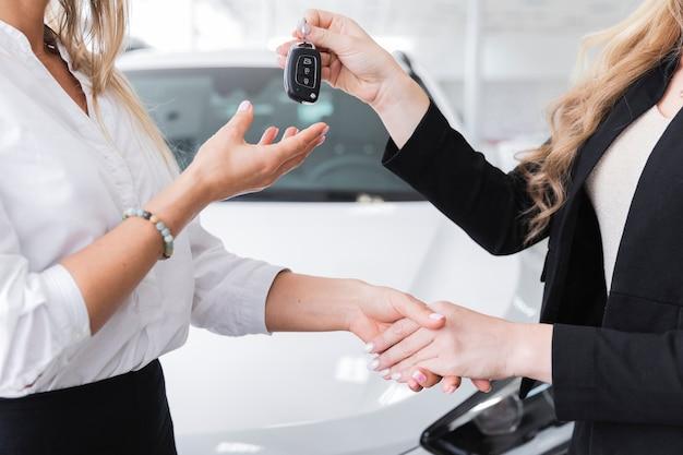 Vista lateral de la mujer que recibe las llaves del auto