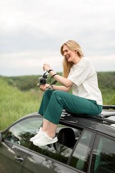 Vista lateral de la mujer que sostiene la cámara mientras posa encima del coche