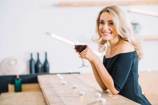 Vista lateral de la mujer que sostiene la copa de vino