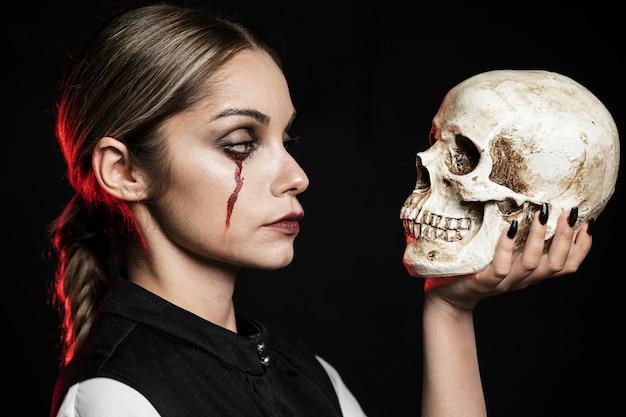 Vista lateral de la mujer que sostiene el cráneo