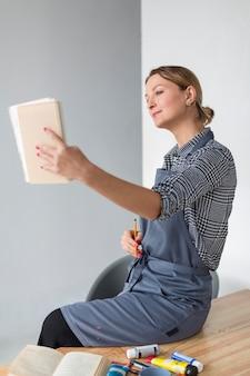 Vista lateral de la mujer que sostiene el cuaderno