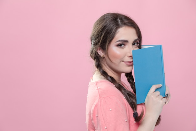 Vista lateral de la mujer que sostiene el libro cerca de la cara