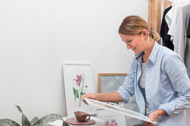 Vista lateral de la mujer que sostiene la pintura de flores