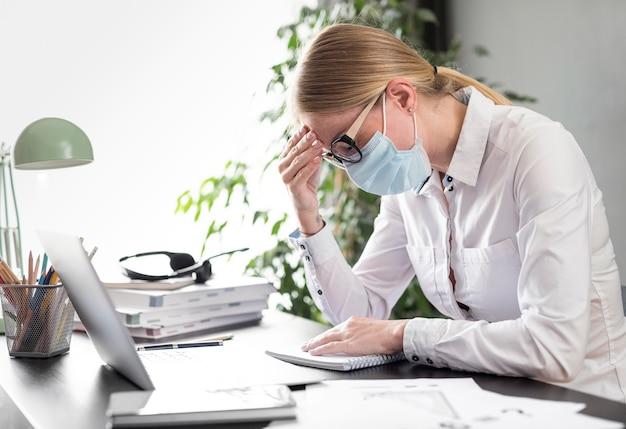 Vista lateral mujer que tiene dolor de cabeza mientras usa una mascarilla