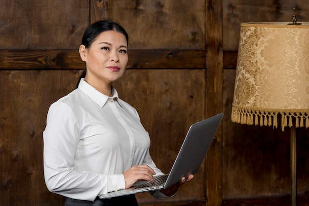 Vista lateral mujer que trabaja en la computadora portátil